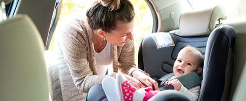 Mom buckling baby into car seat